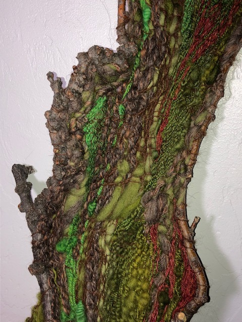 handspun handwoven tapestry on a branch